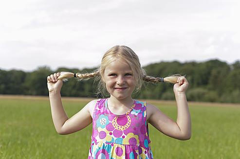 Germany, North Rhine-Westphalia, Hennef, Girl holding her braids in meadow, smiling - KJF000146
