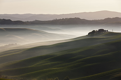 Italy, Tuscany, Crete, View of farm with fog at hilly landscape - FOF003546