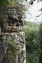 Germany, Rhineland-Palatinate, Eifel Region, South Eifel Nature Park, View of hiker standing on bunter rock formations at beech tree forest - GWF001530