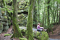 Germany, Rhineland-Palatinate, Eifel Region, South Eifel Nature Park, View of woman hiker sitting on bunter rock formations at beech tree forest - GWF001536
