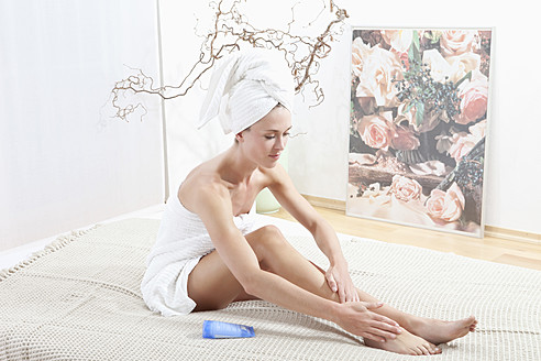 Young woman wrapped in towel applying body cream - MAEF003681