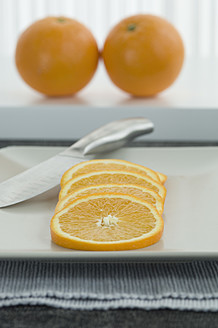 Whole orange with slices on plate, close up - ASF004393