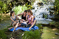 Italy, Tuscany, Friends with champagne sitting on grass and having picnic - HSIF000130