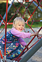 Germany, Munich, Girl climbing on climbing frame in playground, smiling, portrait - HSIF000128