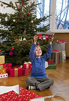 Germany, Munich, Boy sitting christmas present holding toy fire engine - HSIF000142
