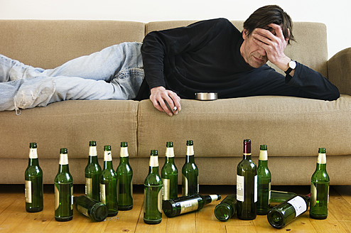Germany, Hessen, Frankfurt, Drunk man lying on sofa with empty beer bottles - MUF001039
