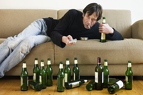 Germany, Hessen, Frankfurt, Drunk man lying on sofa with empty beer bottles - MUF001041