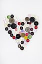 Colourful buttons arranged in heart shape on white background - MUF001063
