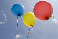 Germany, Bavaria, Three coloured balloons in blue sky - CRF002098