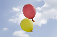 Germany, Bavaria, Red and yellow balloons in blue sky - CRF002103