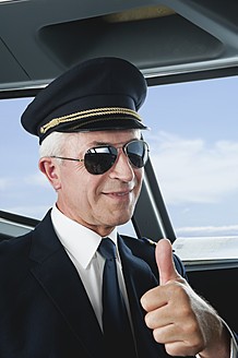 Germany, Bavaria, Munich, Senior flight captain wearing aviation glasses with thumbs up in airplane cockpit, smiling, close up - WESTF017022