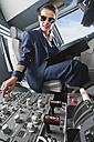 Germany, Bavaria, Munich, Woman flight captain piloting aeroplane from airplane cockpit - WESTF017034