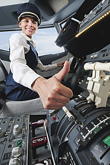 Germany, Bavaria, Munich, Woman flight captain with thumbs up in airplane cockpit - WESTF017040