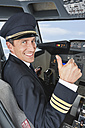 Germany, Bavaria, Munich, Pilot with thumbs up in airplane cockpit - WESTF017052