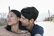 Spain, Majorca, Young man embracing woman on boardwalk at beach - WESTF017109