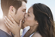Spain, Majorca, Young couple kissing on boardwalk, close up - WESTF017127