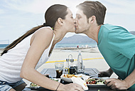 Spain, Majorca, Young couple kissing at dinner near beach - WESTF017130