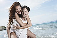 Spain, Majorca, Young man carrying woman on back at beach - WESTF017133