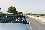 Spain, Majorca, Young couple travelling in cabriolet car - WESTF017160