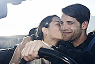 Spain, Majorca, Young woman kissing man in cabriolet car, close up - WESTF017169