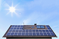 Germany, Solar panels on houseroof in front of blue sky with sun - TSF000345