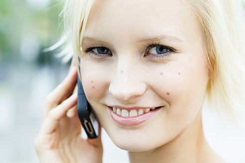 Germany, Bavaria, Munich, Young woman on phone, smiling, portrait - SPOF000042