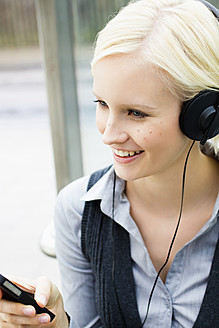 Germany, Bavaria, Munich, Young woman listening music, smiling - SPOF000048