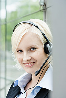 Germany, Bavaria, Munich, Young woman with headset, smiling, portrait - SPOF000057
