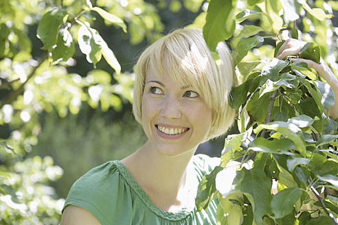 Germany, Bavaria, Schaeftlarn, Close up of young woman in park, smiling - TCF001771