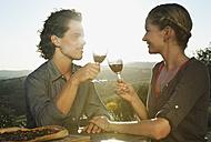 Italy, Tuscany, Young couple clinking wine glasses at dusk - PDF000206