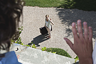 Italy, Tuscany, View of young woman with luggage from hotel window - PDF000246