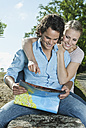 Italy, Tuscany, Young couple sitting on stone wall with map - PDF000271