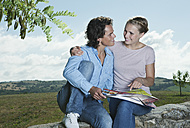 Italy, Tuscany, Young couple sitting on stone wall with map - PDF000277