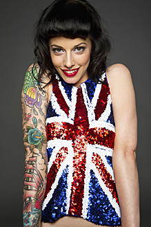 Young woman with tattoo on her hand against grey background, smiling, portrait - MBE000193