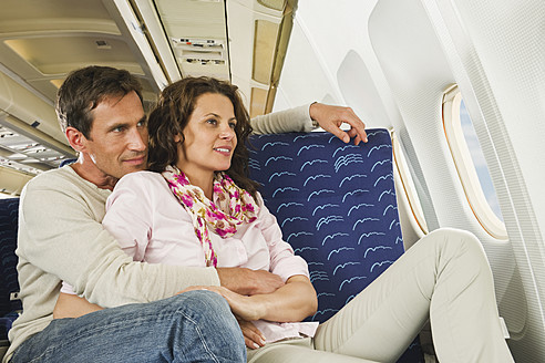 Germany, Munich, Bavaria, Mid adult couple looking out through window in economy class airliner - WESTF017211