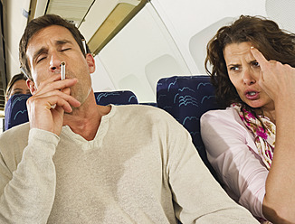 Germany, Munich, Bavaria, Man smoking and women getting annoyed in economy class airliner - WESTF017217