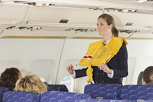 Germany, Munich, Bavaria, Stewardess guiding passengers with life vest in economy class airliner - WESTF017256