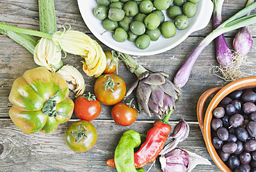 taly, Tuscany, Magliano, Olives in bowl, spring onions, tomatoes, garlic, peppers and artichoke on wooden table - WESTF017330