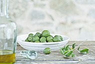 Italy, Tuscany, Magliano, Green olives in plate and jar of olive oil - WESTF017336