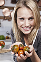 Italy, Tuscany, Magliano, Close up of young woman holding tomatoes in kitchen, smiling, portrait - WESTF017417