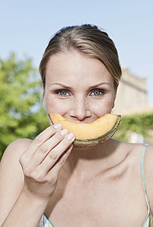 Italy, Tuscany, Magliano, Close up young woman eating honey melon, portrait - WESTF017435