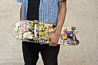 Germany, Düsseldorf, Close up of skateboarder holding his deck in public skatepark - KJF000152