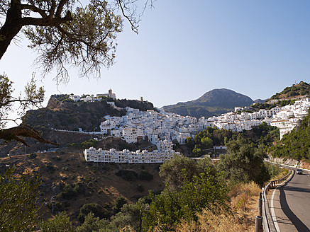 Spain, Andalusia, Casares, View of white houses of mountain village with road - BSCF000057