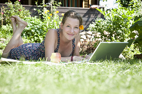Germany, Hamburg, Woman lying on grass and using laptop at allotment garden - DBF000186