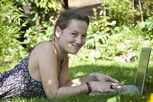 Germany, Hamburg, Woman lying on grass and using laptop at allotment garden - DBF000187