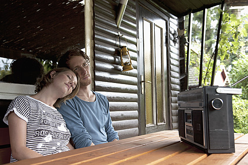 Germany, Hamburg, Man and woman listening to radio in cottage at allotment garden - DBF000195