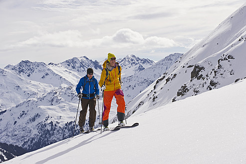 Austria, Stuben, Young couple doing telemark skiing on arlberg mountain - MIRF000298