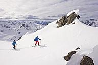 Austria, Stuben, Young couple doing telemark skiing on arlberg mountain - MIRF000301