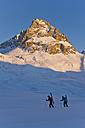 Austria, Zuers, Telemark skiers walking in Arlberg mountain snow - MIRF000331