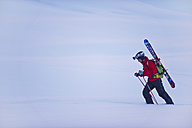 Austria, Zuers, Young man doing telemark skiing on Arlberg mountain - MIRF000334